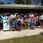 A group of children and adults with a sign for Reef Catchments.